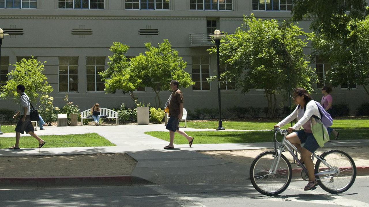 people walking and biking in front of campus building