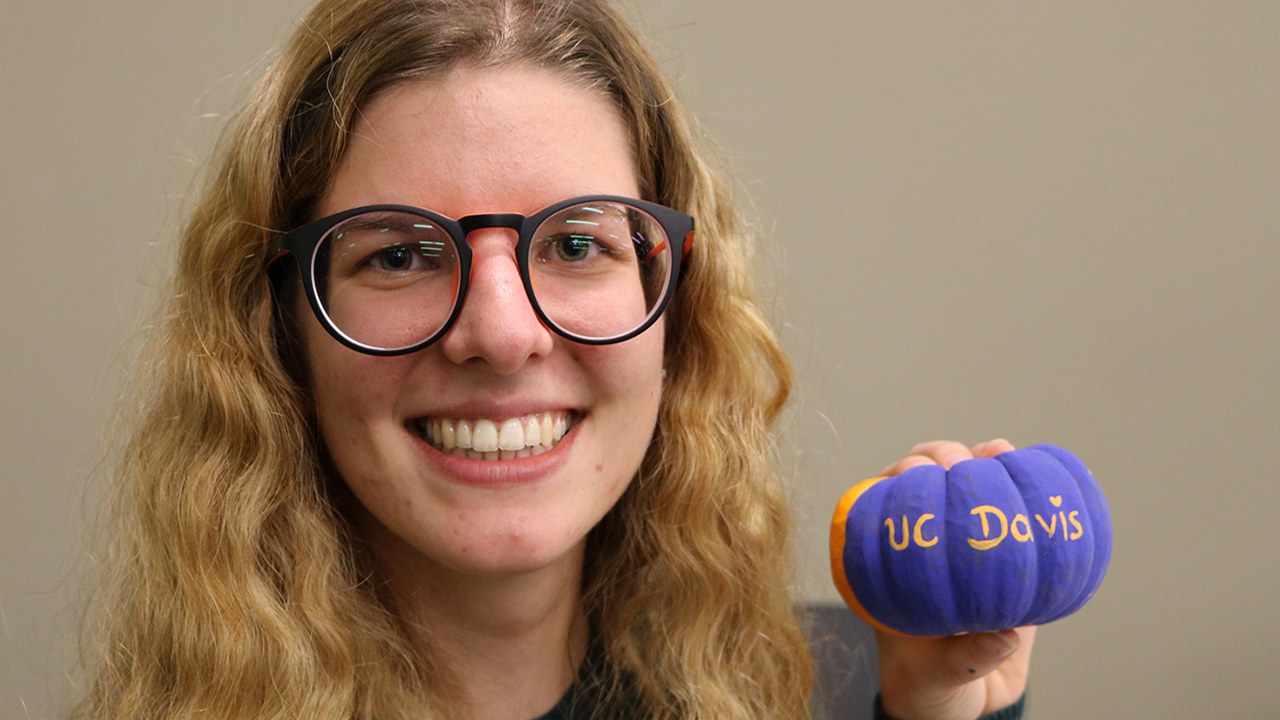 girl holding a pumpkin painted with UC Davis logo