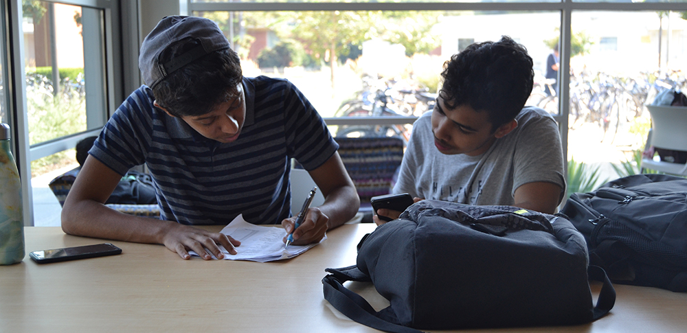 two male students studying at table