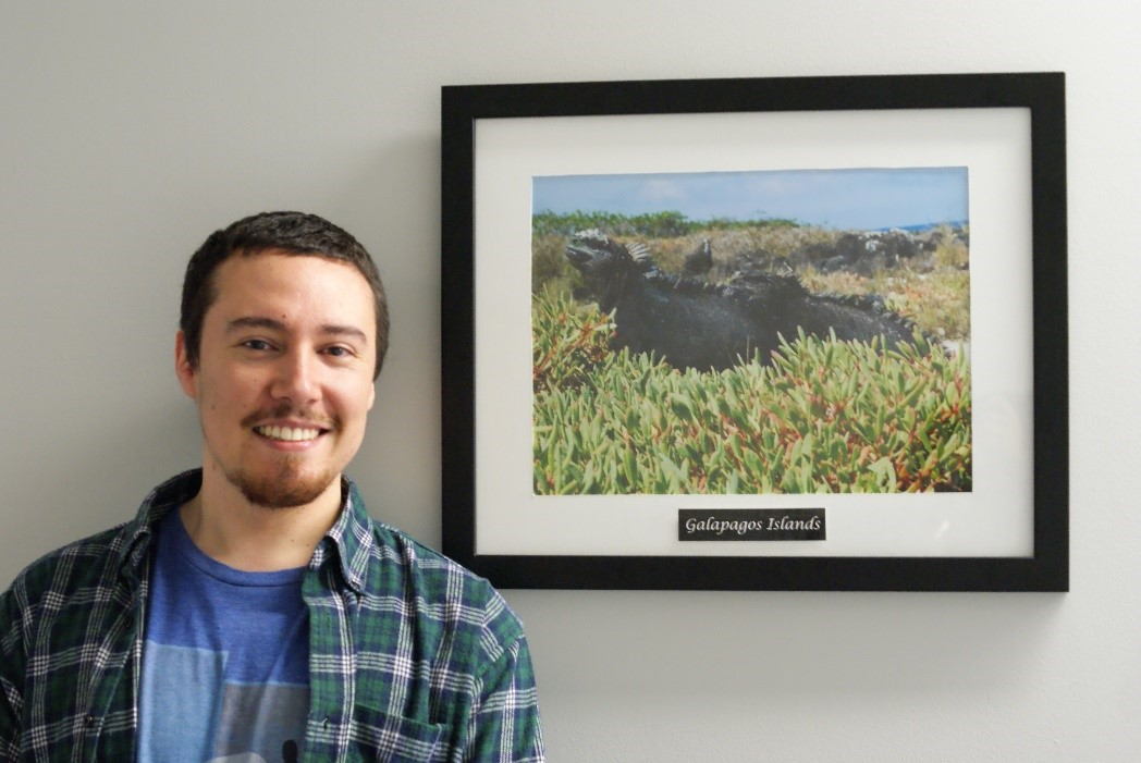 IEP Student Francisco Astorga poses with a photo of an Iguana from Galapagos Island