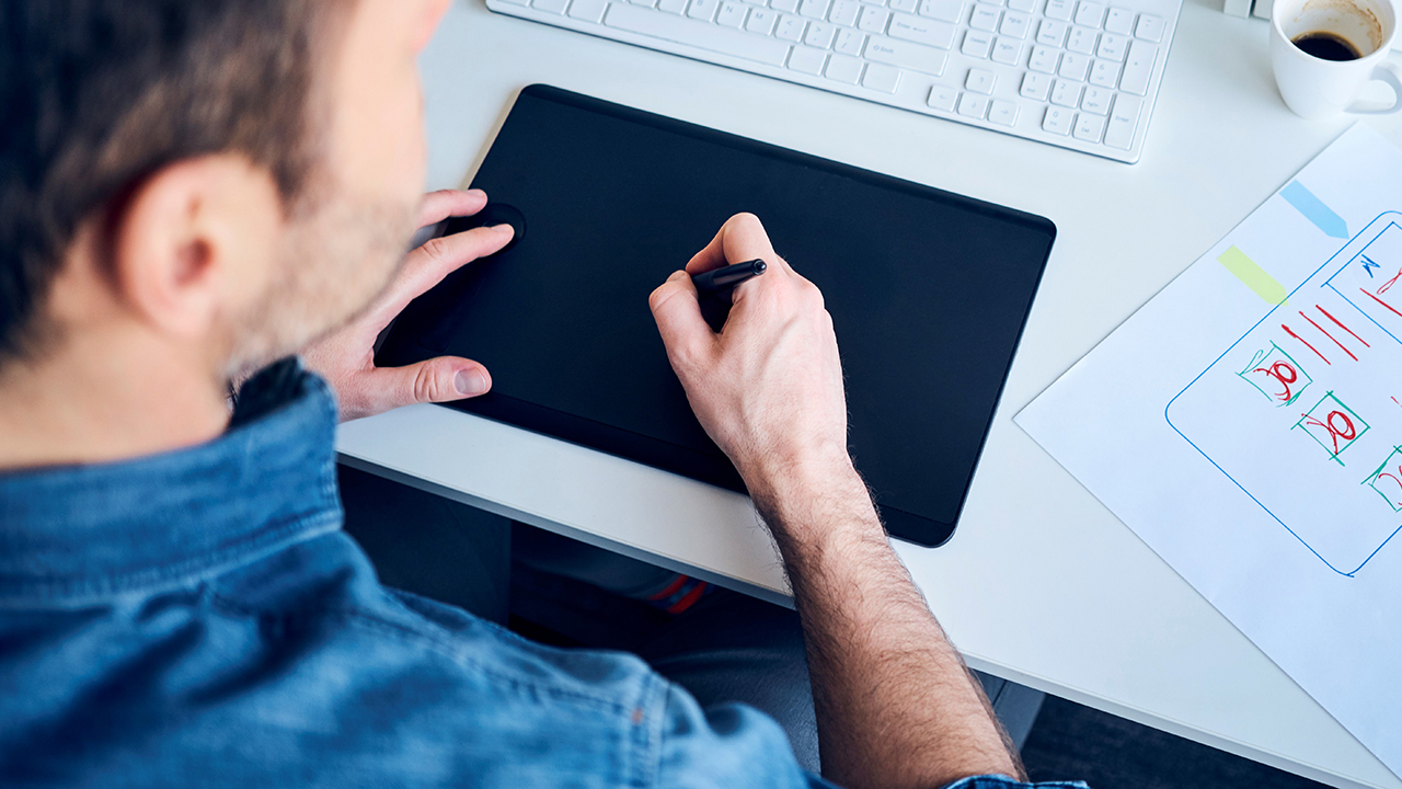 man looking at wireframe diagram and drawing on tablet computer