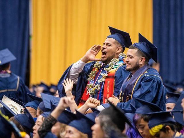 a student cheers at the College of Letters & Science commencement in June (UC Davis photo)