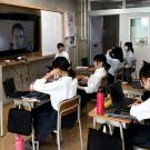 high school students in classroom listen to a lecture on an overhead screen